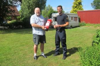 Peter Håkansson lämnar över en handbrandsläckare till Bengt Lindblom i Asarum som tack för hjälpen vid insatsen i Tararp 12/5.