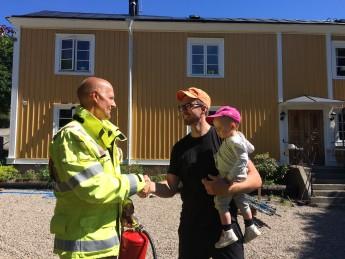 Christer Amundsson lämnar över en handbrandsläckare som tack för hjälpen till Patrik Enarsson. På bilden syns också Patrik och Marias dotter Lova.